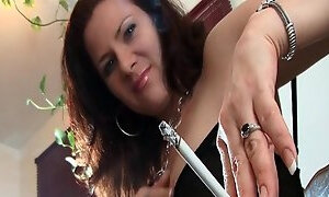 Naughty redhead in black lingerie smokes cigarette