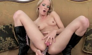 Solo blonde in high heeled boots makes love to glass sex toy close up